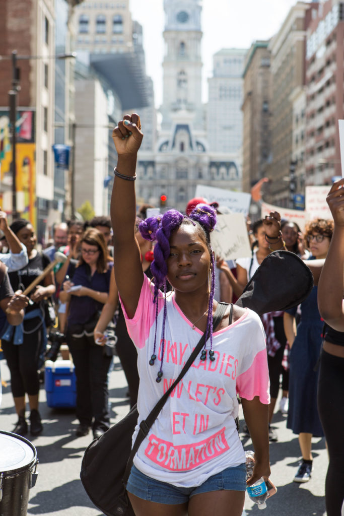 While holding her fist high in the air, this march participant made her way up Broad Street with the rest of the march participants earlier this afternoon.