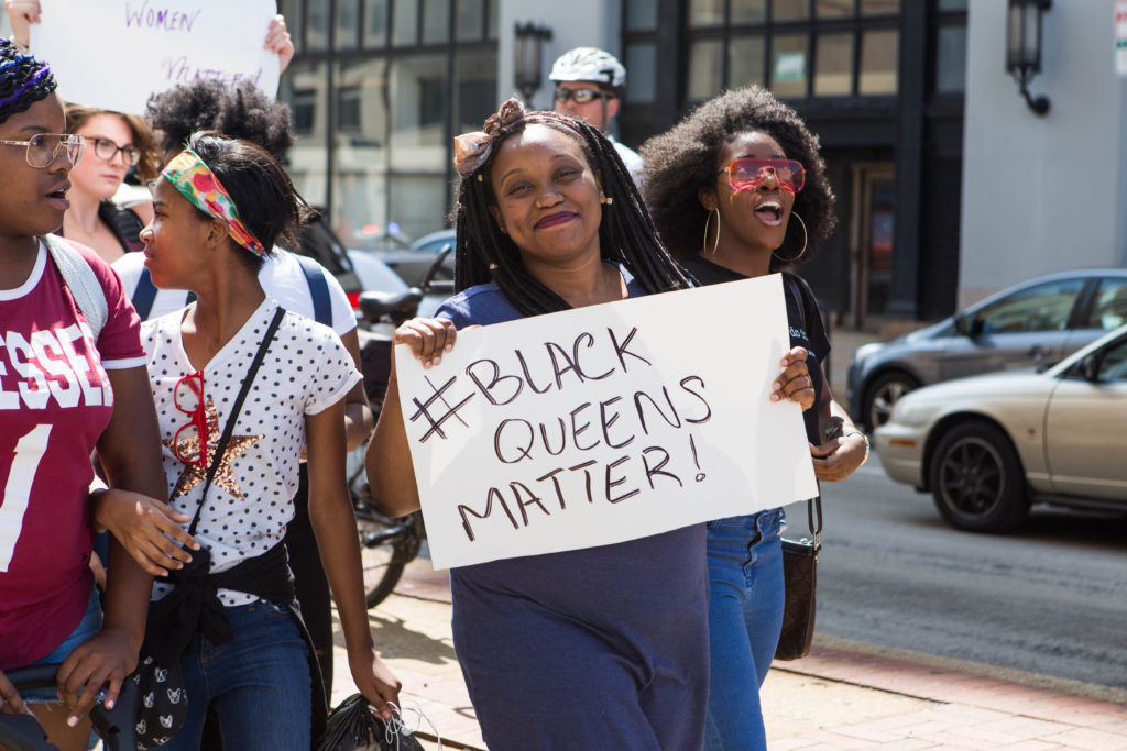 """A march participant holds a sign reading """"#BLACK QUEENS MATTER"""" while making her way up Broad Street with the rest of the participants earlier this afternoon."""
