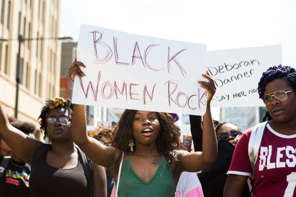 """A march participant holds up a sign reading """"BLACK WOMEN ROCK"""" while chatting """"Black Girls Matter"""" along with the rest of the participants as the march made its way up Broad Street earlier this afternoon."""