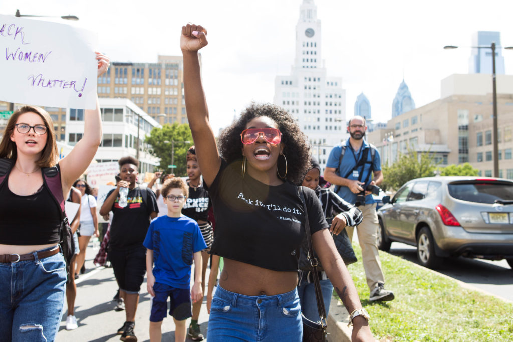 A march participant holds up her fist while chatting along with the crowd as they all made their way up Broad Street earlier this afternoon.