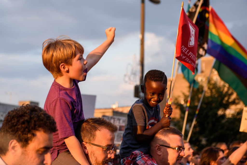 "Oakley, 7, chants, ""Black lives matter"" alongside his friend Gebre, 5, as both are carried by the fathers during the  ""Philly Is Charlottesville"" rally  on Wednesday, August 16, 2017. George Ciccarliello and Benjamin Hover don't doubt their children can grasp what is happening around them and felt it was important for them to learn about human rights."