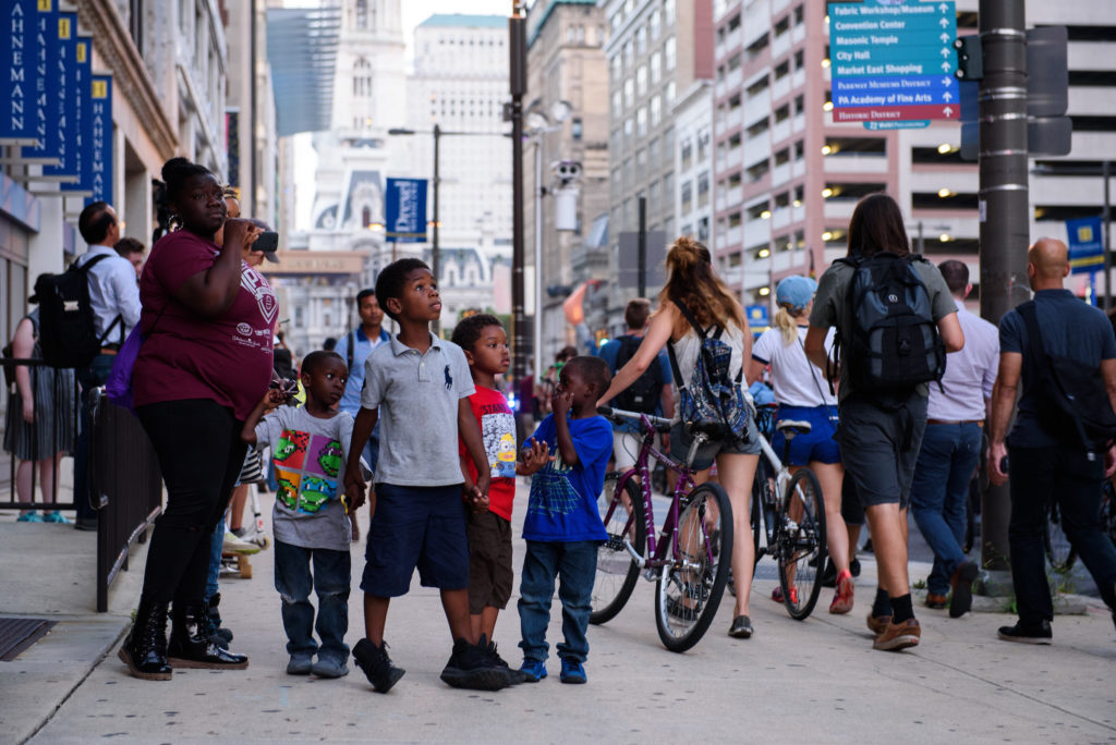 "Breonna Register stands with her and a friends children on North Broad Street as protestors with the ""Philly Is Charlottesville"" rally pass by on Wednesday, August 16, 2017."