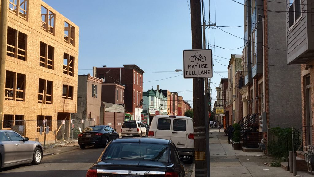A new sign reminds drivers that cyclists can use the full lane on 15th Street in South Philadelphia.