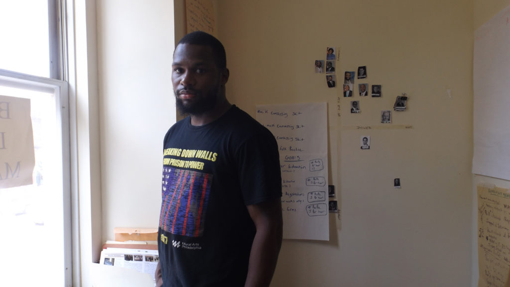Josh Glenn, standing in front of wall depicting those who stand against and for cash bail at Youth Art and Self Empowerment headquarters in North Philadelphia. Glenn spent 18 months in jail because he couldn't afford to pay $2,000 cash bail. His case was ultimately dismissed.