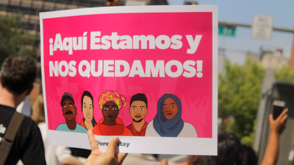 """""""Here we are, and here we stay,"""" reads a sign in Spanish at the march to defend DACA."""