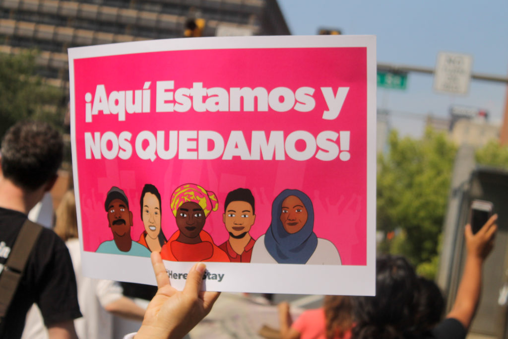 """Here we are, and here we stay,"" reads a sign in Spanish at the march to defend DACA."