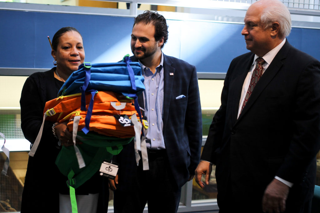 Bryan Leib (center) hands a stack of backpacks to Theresa Knight, a counselor at the Penn Alexander School in West Philadelphia.