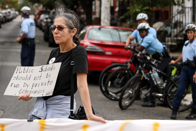 "A demonstrator holds a sign reading, ""public schools should not be run by private companies,"" during a protest in Sharswood."