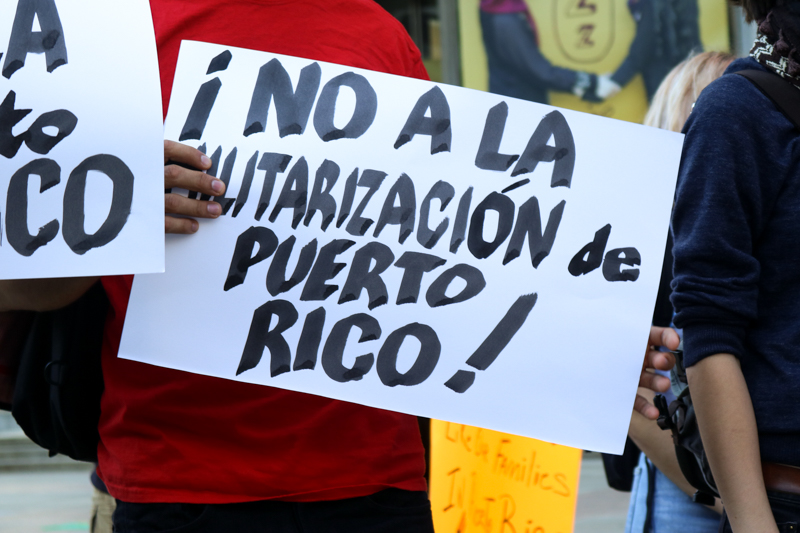 A sign protests militarization in Puerto Rico at a protest at Thomas Paine Plaza on Friday.