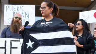 A member of the nonprofit Voces del Barrio carries a black Puerto Rican flag, often used to represent resistance to U.S. policies.