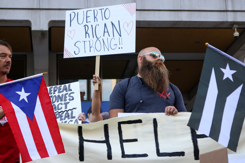 Puerto Rican flags and politically-charged signs adorned Thomas Paine Plaza on Friday at a protest to aid Puerto Rico.