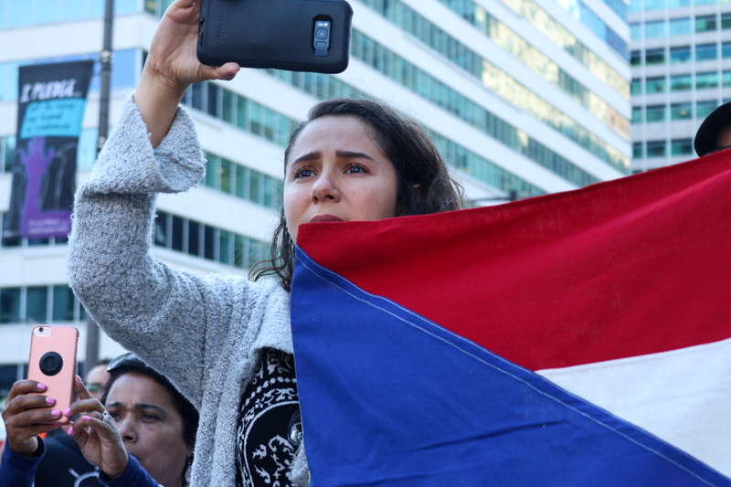 A demonstrator holds a Puerto Rican flag while watching the rally. Puerto Rico's Center for Investigative Journalism has predicted that the island's death tolls are higher than those officially reported.
