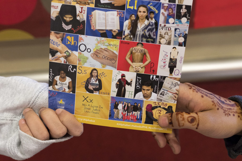 NEHS grads Jenny Lim and Doha Salah hold a promo postcard for 'Immigrant Alphabet'