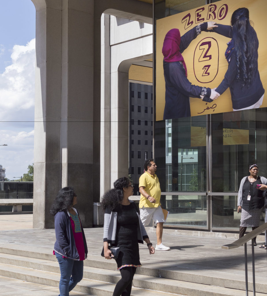 People entering the Municipal Services Building below an art installation called 'Immigrant Alphabet' in 2017