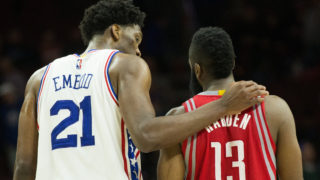 Joel Embiid puts his arm around Houston Rockets guard James Harden