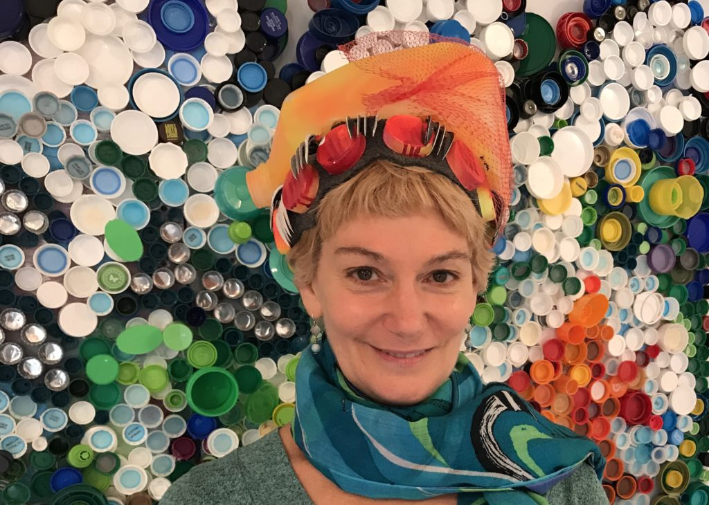 Simone Spicer often wears a plastic hat when looking for plastic to use. In the background is one of her ocean pieces made out of bottle caps.