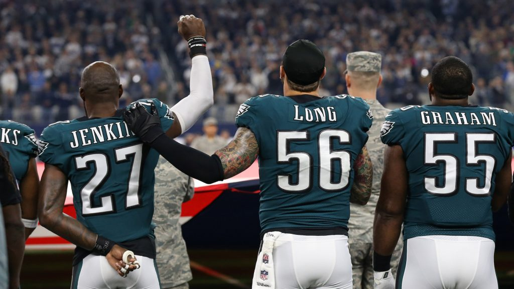 Eagles safety Malcolm Jenkins (left) raises a fist during the national anthem in 2017 as teammate Chris Long  (right) places a hand on his shoulder in solidarity
