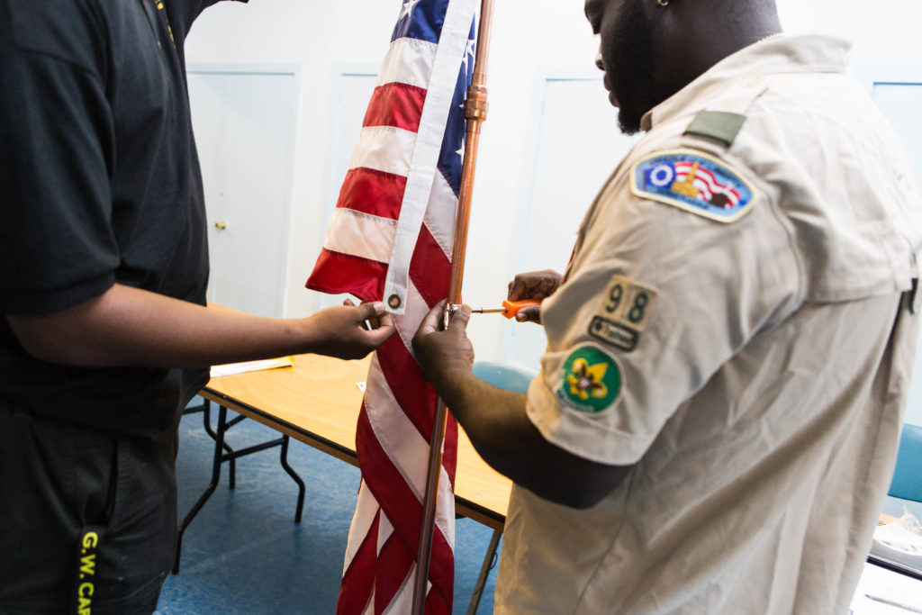 Scout Master Antonio McCall helps one of the scouts set up the flag for their weekly scout meeting.