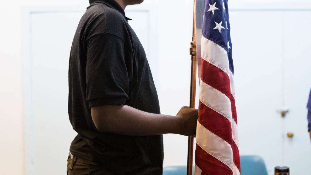 One of Troop 98's scouts holding the flag as their weekly meeting begins.