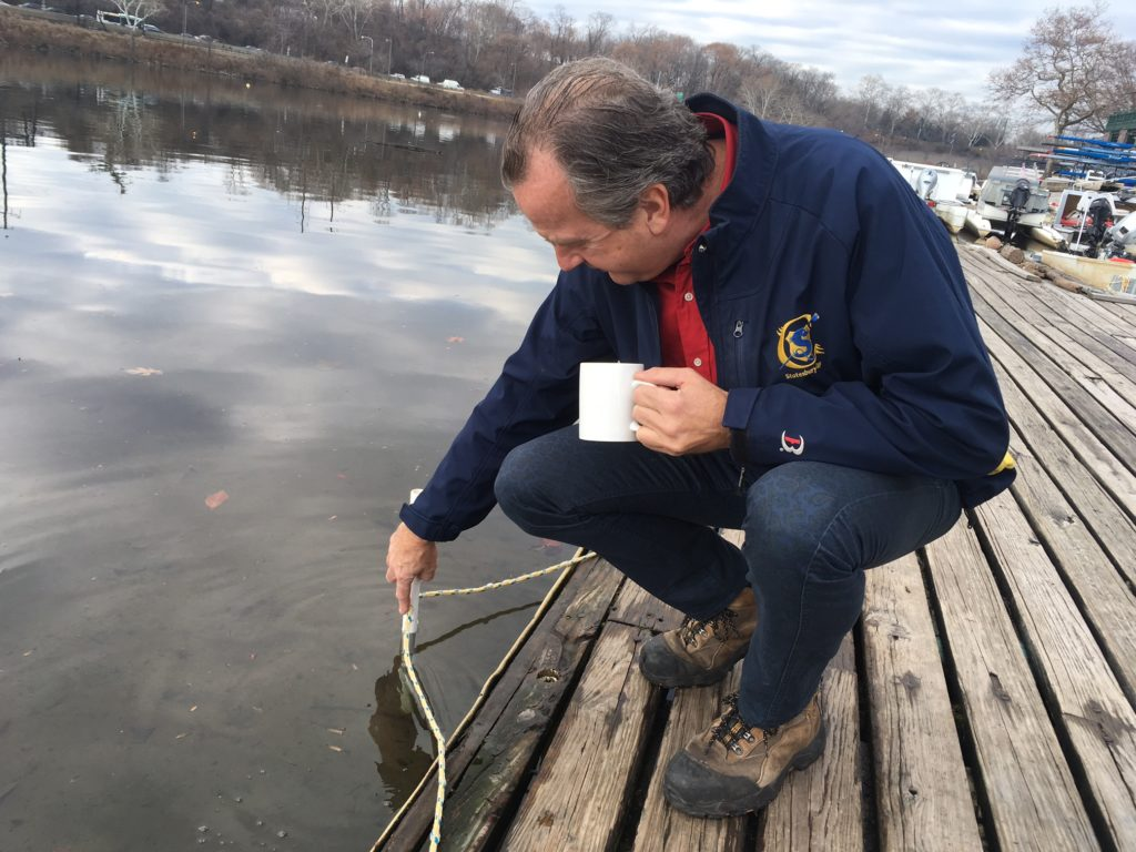 Schuylkill Navy commodore Paul Horvat measures water depth outside Vesper.