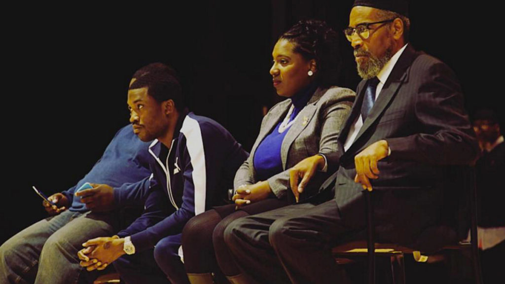Meek Mill sits on stage at a local high school in 2016 with U.S. Rep. Joanna McClinton and music producer Kenny Gamble