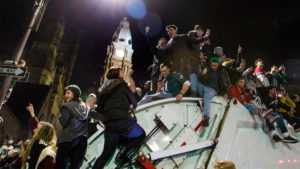 Eagles fans celebrate atop a trash truck (and on a pole) in front of City Hall