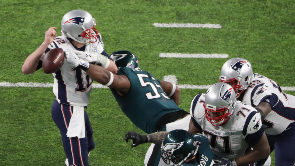 New England Patriots quarterback Tom Brady fumbles the ball as he is hit by Philadelphia Eagles defensive end Brandon Graham during the fourth quarter in Super Bowl LII at U.S. Bank Stadium
