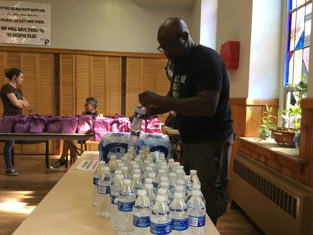 Prevention Point's Clayton Ruley preps the free bottled water, which he hands out every Friday afternoon.