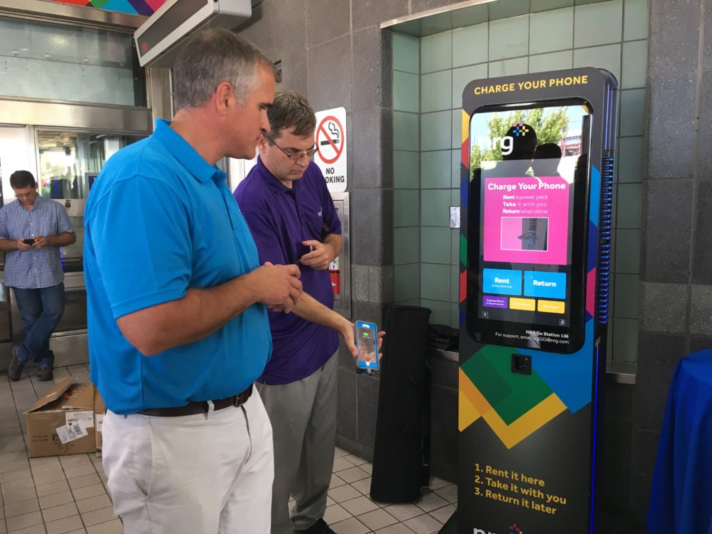 NRG VP and General Manager Mike Starck, left, demonstrates the kiosk that dispenses portable cell phone chargers.