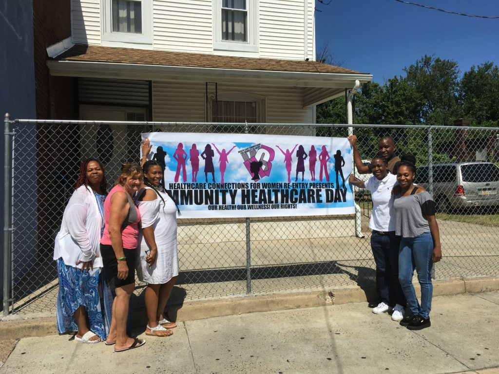 Michelle Simmons, third from left, holds a banner advertising her community health fair with employees, volunteers and residents of Why Not Prosper.