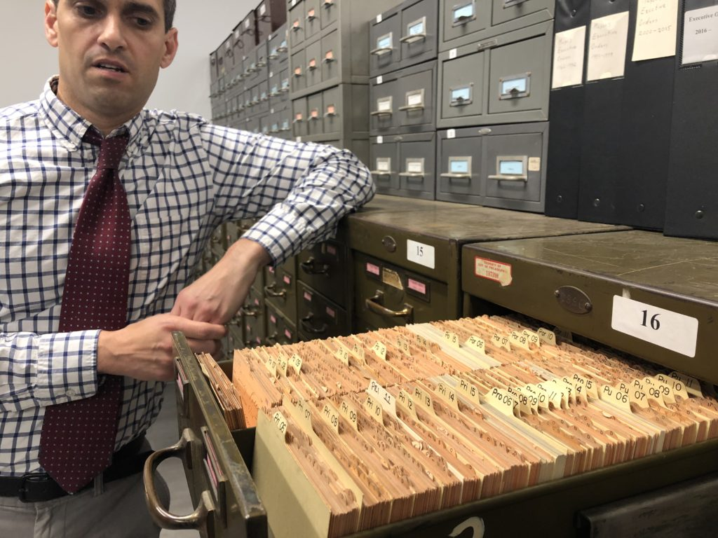 "James Leonard, commissioner of the Department of Records, opening a drawer full of ""death returns."""