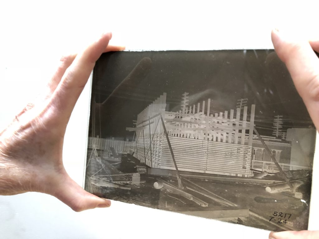 "Archival consultant Jill Rawnsley holding up a glass-plate photograph of ""cooling coils"" from 1918. Location unknown."