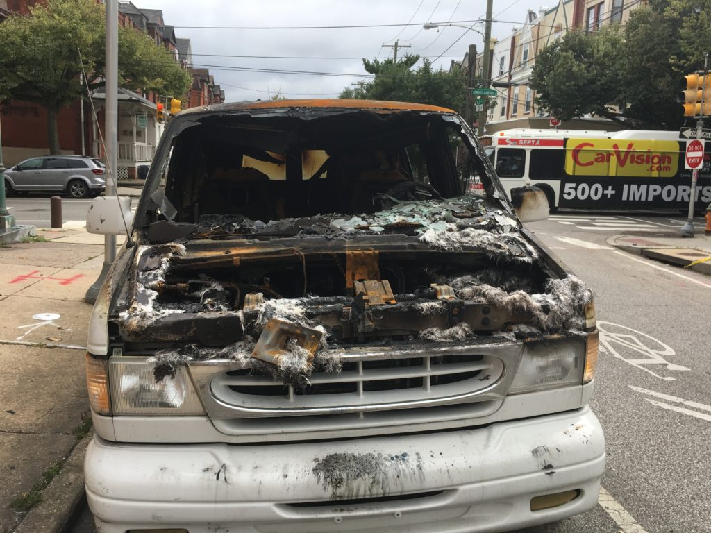 A van parked on 33rd Street, totally torched