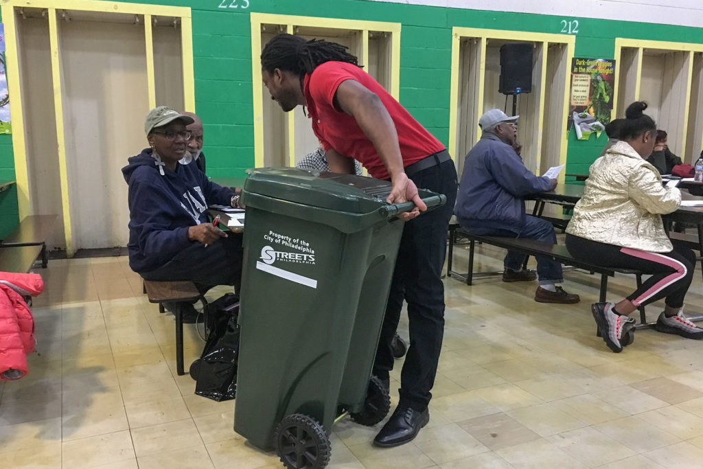 A Streets Dep. staffer shows off a 35-gallon trash can to North Philly residents