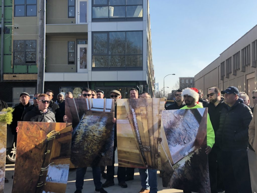 Union workers hold up enlarged photos of alleged mold in the 401 Race Street development.
