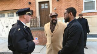 Malik Upshur (right) talks to a 17th district police officer and Councilman Kenyatta Johnson.