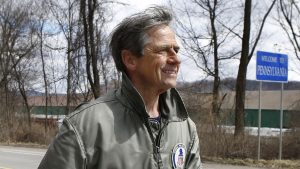 "Former U.S. Rep. Joe Sestak, passing a sign marking the Pennsylvania-Ohio state border at the end of his ""Walking In Other Pennsylvanian's Shoes"" tour in 2015"