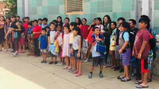 Summer camp attendees pose for a photo outside the El Futuro location.