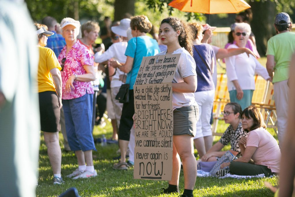 A vigil attendee in Collingswood holds a sign hearkening back to her ancestors' experience