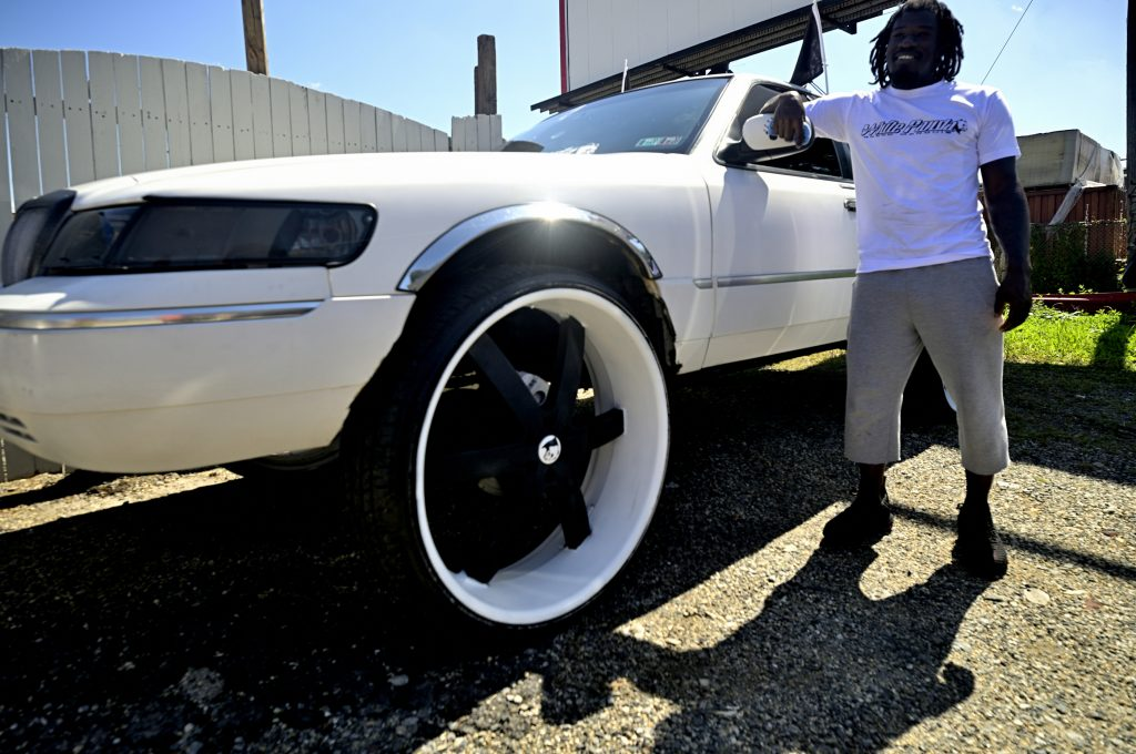 Bruce Davis, 35, of North Philadelphia stands next to a 1998 Mercury Grand Marquis he named White Panda that stands on 30 inch wheels