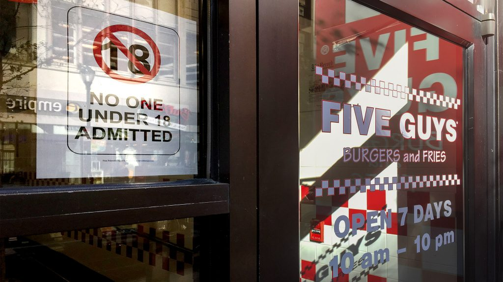 A sign in the door of a Center City Five Guys bans kids under 18 from entry