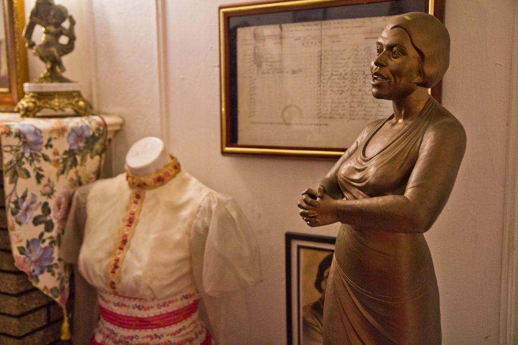 A statuette of Marian Anderson, a gown she performed in, and her birth certificate