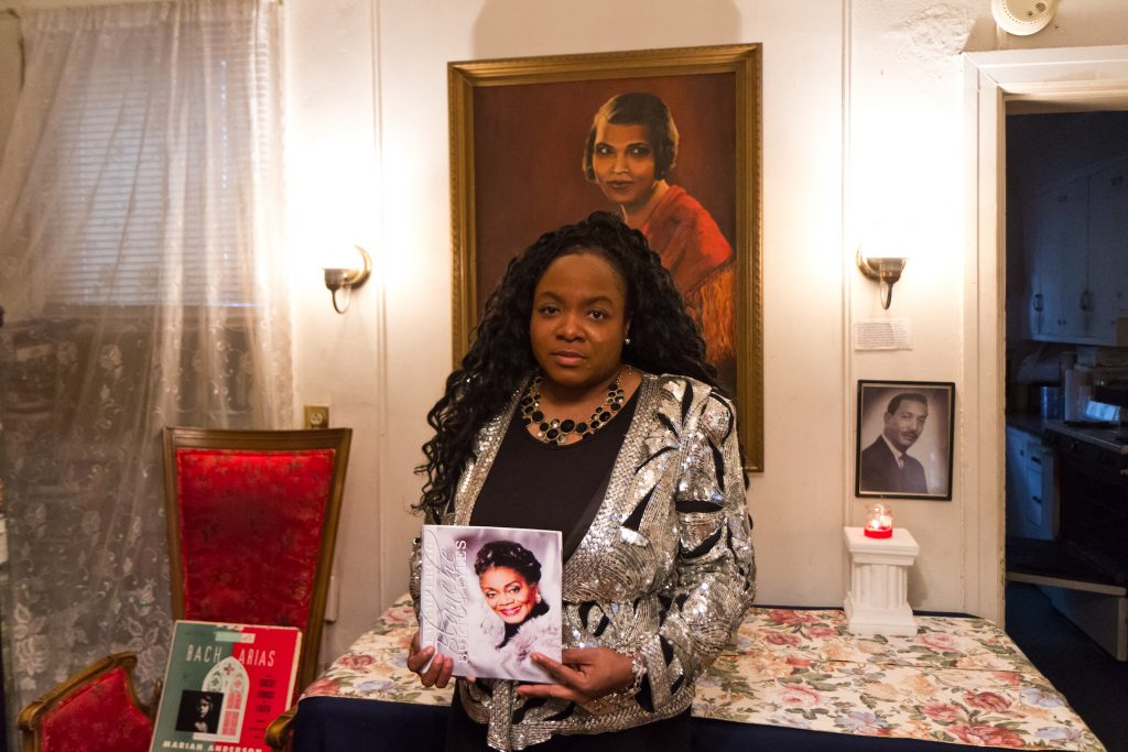 Jillian Patricia Pirtle an opera performer and CEO and owner of the Marian Anderson Museum, holds a photo of her deceased mentor  Blanche Burton-Lyles, classical pianist, in front of a painting of Burton-Lyles' mentor, Marian Anderson