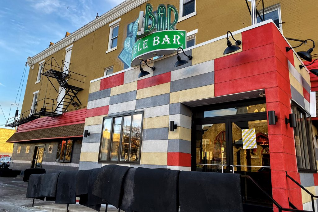 Eagle Bar next to Max's, with newly-cleaned floor mats hanging out to dry