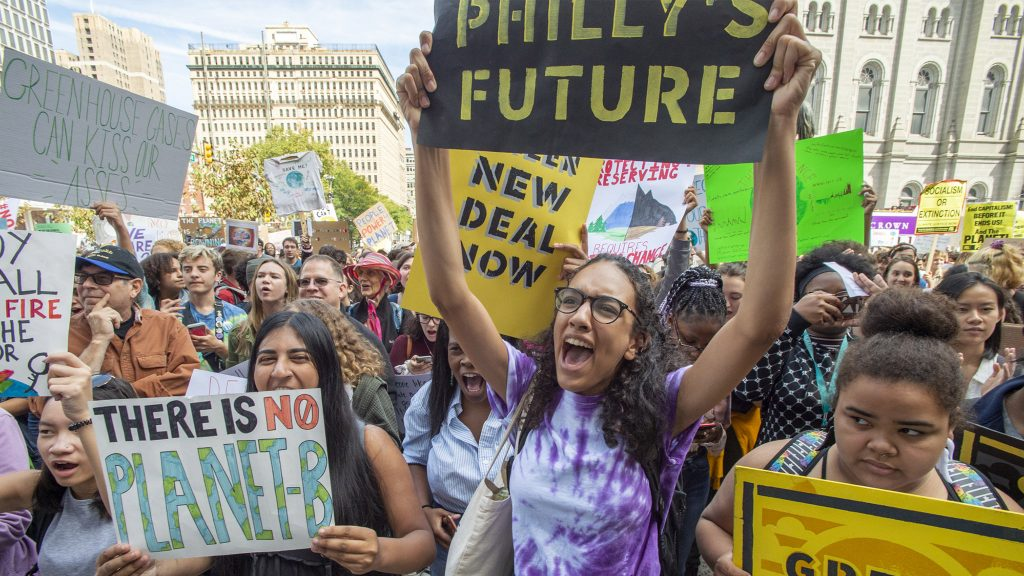 Masterman High School seniors Iman Acharya  and Alina Kilcullen cheer speakers at a climate strike in September