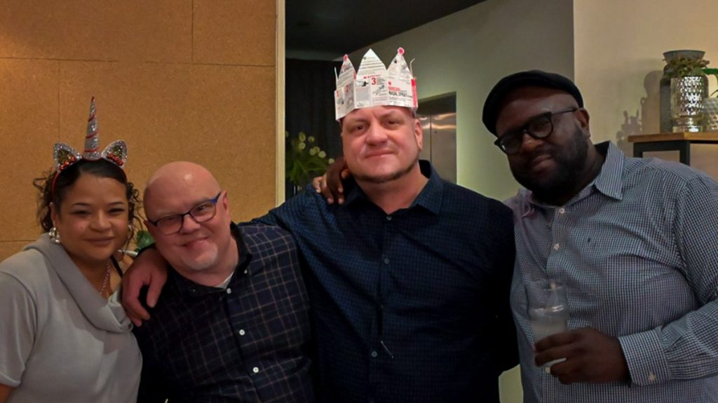 Rosado (center, with crown) surrounded by colleagues at his goodbye party