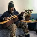 John Oliver, Jr., plays guitar at Hub of Hope's Living Room