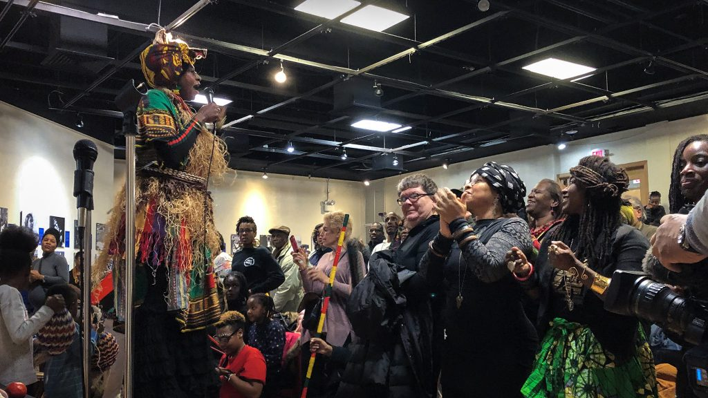 A stilt-walker leads the crowd celebrating Kwanzaa in the auditorium of the African American Museum in Philadelphia