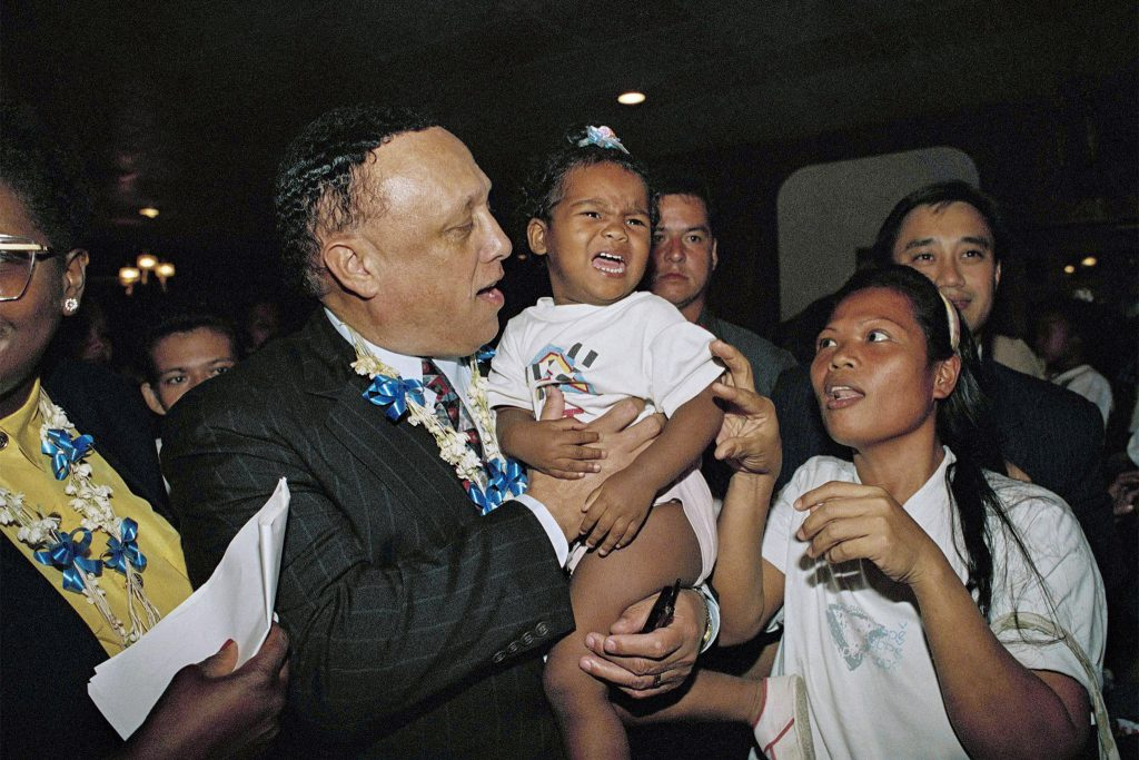 Congressman Lucien Blackwell carries a young girl on Jan. 13, 1994 at the former US naval base near Manila. Blackwell had sponsored a bill seeking an amendment to grant Filipinos American citizenship.