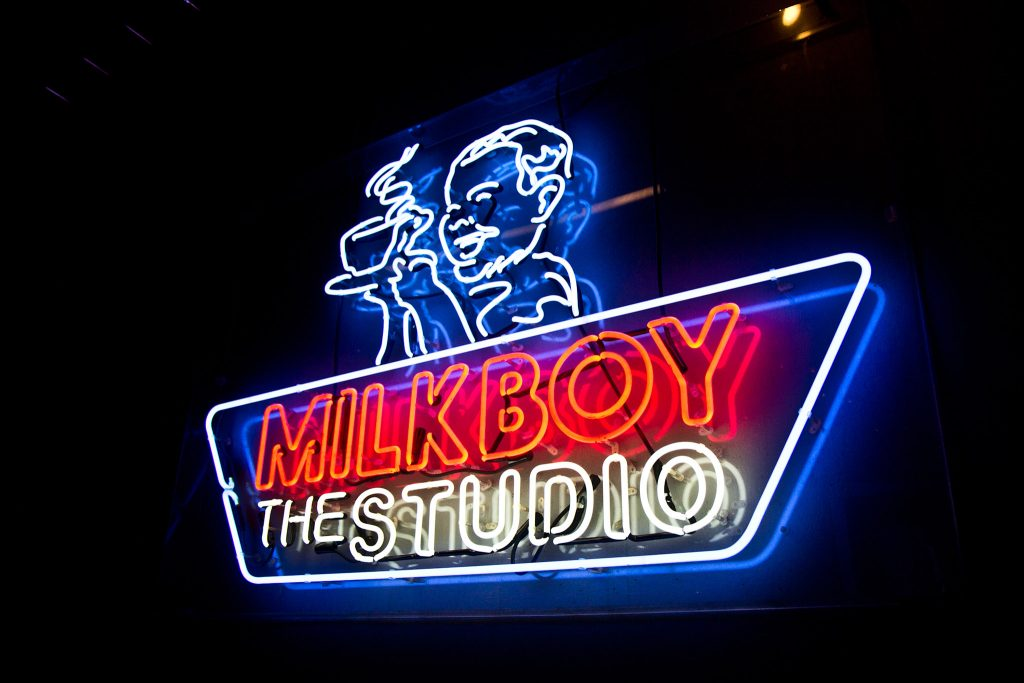 A MilkBoy neon sign greets visitors coming off the elevator